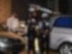 Mitarbeiter einer Beerdigungsfirma tragen eine Leiche unter Schutz von Polizisten zu einem Leichenwagen. Foto: Roberto Pfeil/dpa