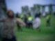 Menschen springen über einen Zaun und bahnen sich ihren Weg an Sicherheitspersonal vorbei in Richtung Stonehenge. Foto: Ben Birchall/PA Wire/dpa