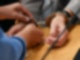 Eine Justizbeamtin nimmt der Angeklagten im Gerichtssaal des Landgerichts Hanau die Handschellen ab. Foto: Arne Dedert/dpa
